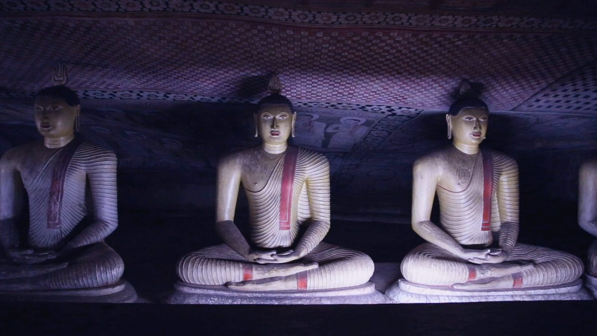 Three cross-legged statues of meditating Buddha